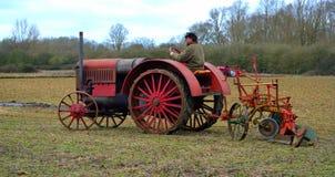 Uitstekend rood Internationaal de tractor ploegend gebied van 1930 ` s Stock Fotografie