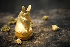 Uitstekend schaakpaard in goud en goud op oude steenvloer Stock Fotografie