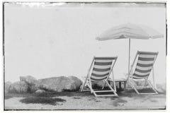 Uitstekend stijl gefiltreerd beeld van twee lege ligstoelen en paraplu op kustlijn stock foto