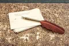 Uitstekend stilleven met oude prentbriefkaaren en veerpen retro st Stock Fotografie