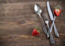 Uitstekend tafelzilver op bruine lijst met aardbei Stock Foto