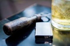 Uitstekend zilveren lichter Flesopener en Glas whisky op Lusje royalty-vrije stock foto's