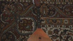 Uitstekende balalaika op de achtergrond van het oude tapijt stock footage