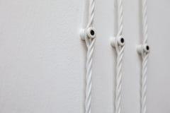 Uitstekende bedrading op witte muur, elektrische draad stock afbeelding