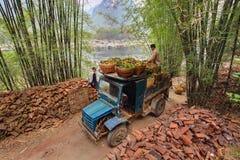 Uitstekende blauwe die vrachtwagen, van sinaasappelen in rieten manden, China wordt geladen. royalty-vrije stock foto's