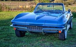 Uitstekende blauwe sportwagen convertibel door een weiland bij zonsondergang Royalty-vrije Stock Foto's