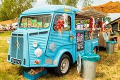 Uitstekende blauwe voedselvrachtwagen op een markt van het land Stock Fotografie