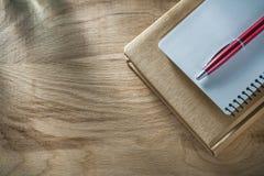 Uitstekende blocnotespen op houten raad stock foto
