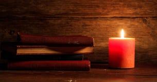 Uitstekende boeken en een kaars op houten achtergrond Stock Afbeelding