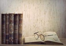 Uitstekende boeken en glazen stock foto