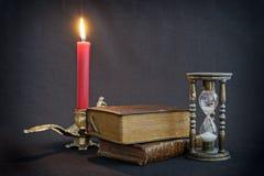 Uitstekende boeken en zandloper Stock Foto