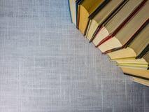 Uitstekende boeken gestapelde zij aan zij ontwerpende open witte stoffenachtergrond voor exemplaar stock fotografie
