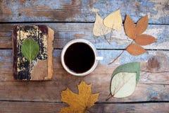 Uitstekende boeken, kop van koffie en de herfstbladeren op houten bureau Royalty-vrije Stock Foto's