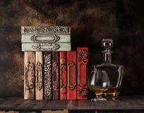 Uitstekende boeken op een plank en een cognac in een glas en een fles royalty-vrije stock foto's