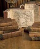 Uitstekende boeken oude kaarten op een houten lijst royalty-vrije stock afbeelding