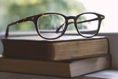 Uitstekende bril op boeken naast een venster Stock Foto's