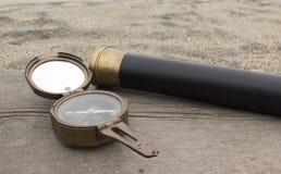 Uitstekende bronskompas en kijker op de achtergrond van het overzees Stock Foto's