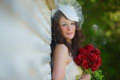 Uitstekende bruid met rood boeket Stock Fotografie