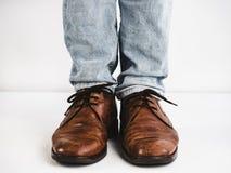 Uitstekende, bruine schoenen, jeans en mensen` s voeten Stock Fotografie