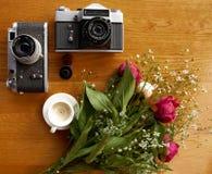 Uitstekende camera dichtbij een boeket van bloemen en kaarsen stock foto's