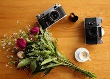 Uitstekende camera dichtbij een boeket van bloemen en kaarsen Stock Foto