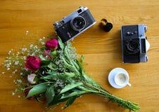 Uitstekende camera dichtbij een boeket van bloemen en kaarsen royalty-vrije stock foto