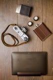 Uitstekende camera en leerriem op houten vloer Stock Afbeeldingen