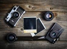 Uitstekende camera met lenzen en lege oude foto op houten achtergrond stock fotografie