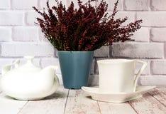 Uitstekende ceramische witte kop en theepot op witte houten achtergrond met heide, exemplaarruimte royalty-vrije stock foto