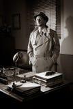 Uitstekende detective die zich in zijn bureau bevinden Stock Afbeelding