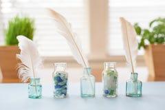 Uitstekende die glasflessen met seaglass en witte veren worden gevuld Stock Afbeelding