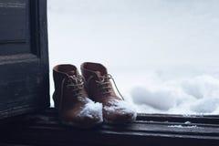 Uitstekende die leerschoenen in sneeuw door de deur worden behandeld stock afbeelding