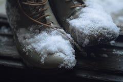 Uitstekende die leerschoenen in sneeuw door de deur worden behandeld stock foto