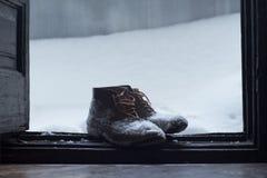Uitstekende die leerschoenen in sneeuw door de deur worden behandeld stock foto's