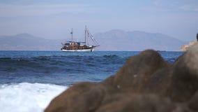 Uitstekende die schoener in het overzees wordt verankerd De golven raken de stenen in de voorgrond stock videobeelden
