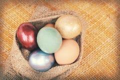 Uitstekende document textuur, kleurrijke paaseieren in zakzak op weefsel Stock Foto's