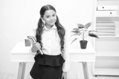 Uitstekende eerste eerstgenoemde De greepboek van het meisjeskind terwijl het witte binnenland van de tribunelijst Schoolmeisje d stock afbeeldingen