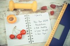 Uitstekende foto, Elektronische badkamersschaal en nieuwe die jaarresoluties in notitieboekje wordt geschreven stock foto's