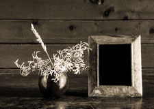 Uitstekende foto-kader en ikebana op oude lijst Stock Foto