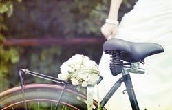 Uitstekende foto van bruid en huwelijksboeket op een fiets Royalty-vrije Stock Fotografie
