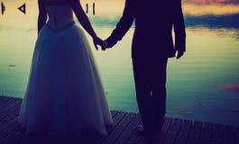 Uitstekende foto van de silhouetten van het huwelijkspaar in openlucht Stock Afbeeldingen