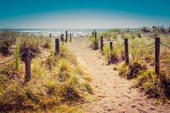 Uitstekende foto van een zandige weg met grasriet en houten posten aan elke kant die tot een mooie baai met rust leiden royalty-vrije stock afbeelding