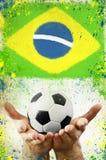 Uitstekende foto van handen die voetbalbal en de vlag van Brazilië houden Royalty-vrije Stock Afbeelding