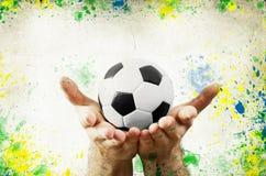 Uitstekende foto van handen die voetbalbal en de vlag van Brazilië houden Stock Foto's