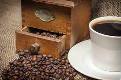 Uitstekende foto van koffiekop en oude koffiemolen Royalty-vrije Stock Foto's