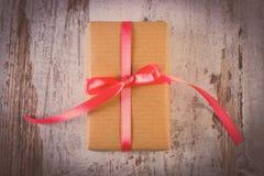 Uitstekende foto, Verpakte gift voor Valentijnskaartendag op oude houten lijst Stock Fotografie