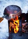Uitstekende gietlepel met hete overwogen wijn op een brand Stock Foto's