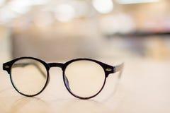 Uitstekende glazen, op houten lijst, die het onderzoeken bestuderen learning stock foto