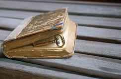 Uitstekende gouden sleutel binnen een sjofel geslagen oud boek royalty-vrije stock fotografie