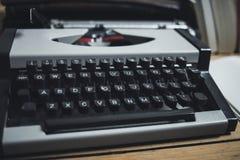 Uitstekende grijze schrijfmachine op de houten vloer Stock Foto